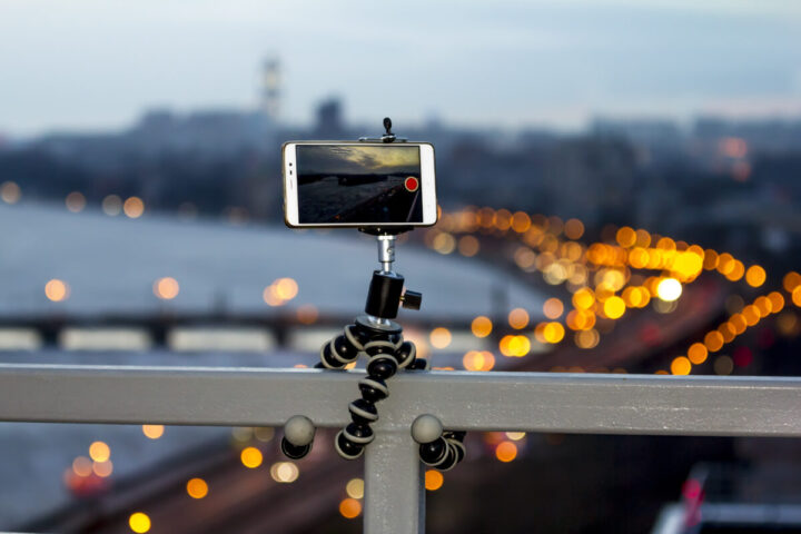 The smartphone is fixed on a tripod shooting a video