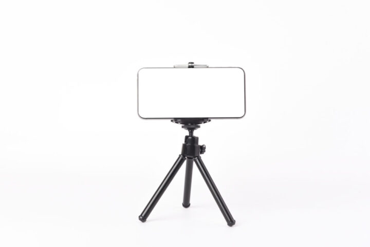 Mobile phone set on tripod for taking pictures,white isolated background.