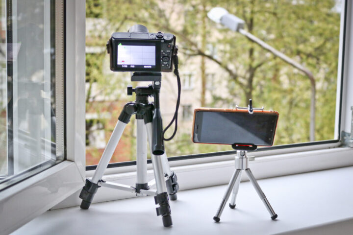 Camera and smartphone on tripods in front of an open window. Time lapse photography - smartphone vs camera.