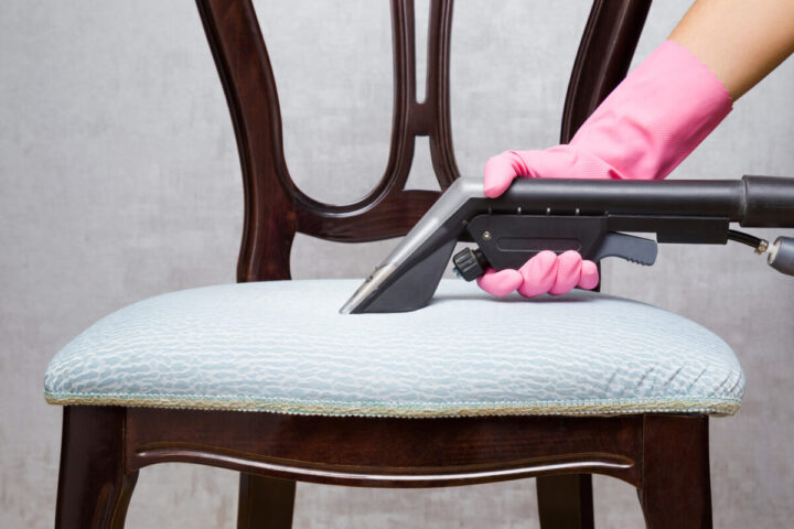 Employee hand in pink protective glove cleaning textile chair with professionally extraction method. Regular cleanup. Commercial cleaning company. Front view.