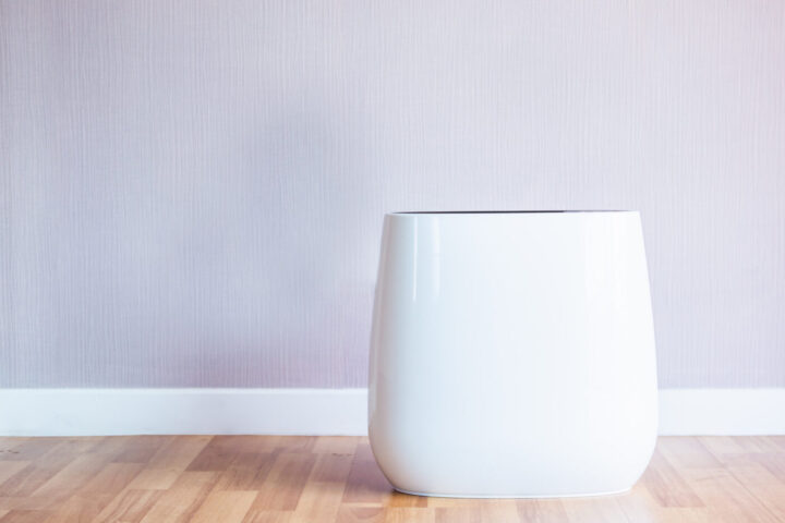 Modern and smart air purifier machine in the living room with empty wall in background, air purifier can helps people from air pollution in their home.