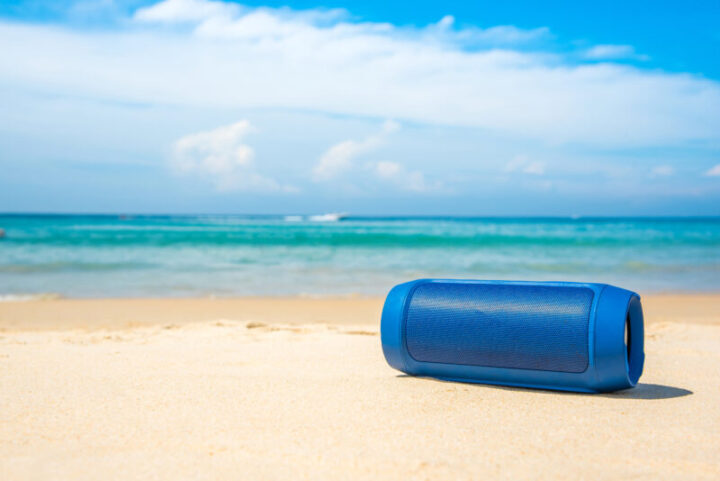 Portable wireless speakers on the beach and blue sky.