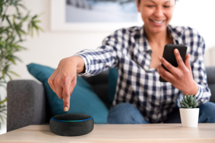 Black woman connecting phone to her virtual assistant smart speaker