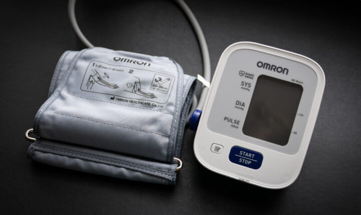 VLADIVOSTOK, RUSSIA - MAY 17, 2018: Electronic tonometer made by Omron for blood pressure measurement on a dark background.